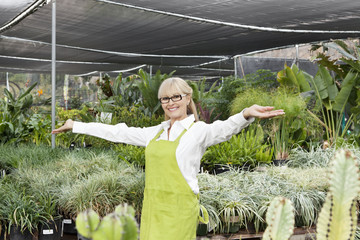 Portrait of a senior woman standing with arms outstretched in garden center