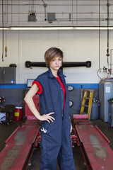 Portrait of a young female mechanic standing with hand on hip in car workshop