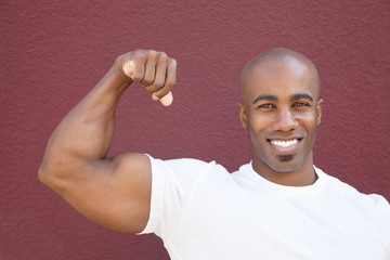 Portrait of a young African American man flexing muscles over colored background