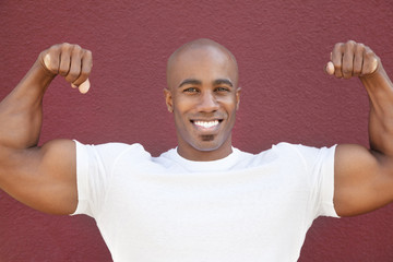 Portrait of a happy African American man flexing muscles over colored background