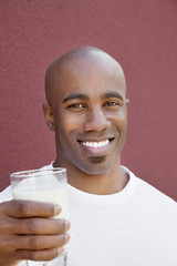 Portrait of a happy young man with milk glass over colored background