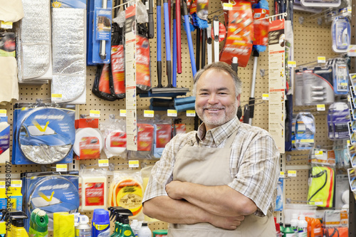 Portrait of a happy mature salesperson with arms crossed in hardware store