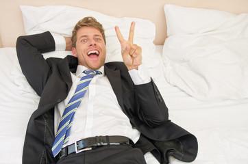 Mann im Bett gibt Handzeichen