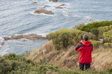 Man with red jacket at the coast