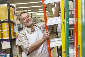 Portrait of a happy mature man with ladder in hardware store