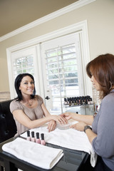 Mid adult manicurist polishing nails of beautiful happy female
