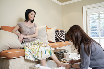 Beautiful mid adult woman sitting in beauty salon while having a pedicure