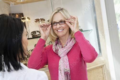 Happy senior woman trying on glasses in store