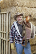 Portrait of happy cowboy carrying riding tack on shoulder