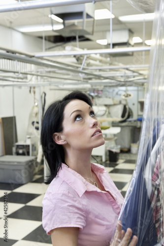 Beautiful mid adult woman putting plastic to dry cleaned while looking up