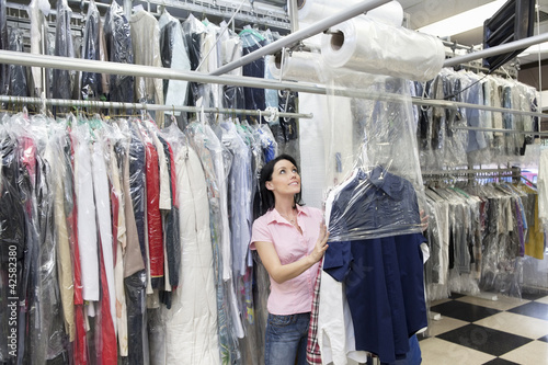 Happy mid adult woman looking up while putting clothes in plastic