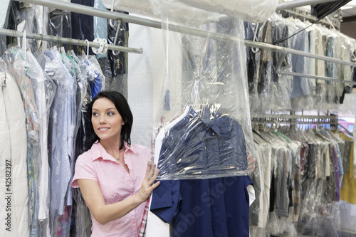 Happy mid adult woman looking away while putting clothes in plastic