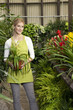 Portrait of a happy young woman standing with potted plant in greenhouse
