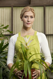 Portrait of a young woman holding potted plant