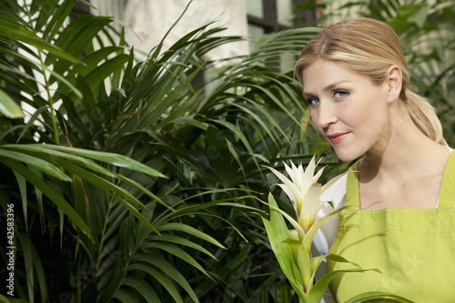 Portrait of a young woman smelling flower in garden center