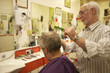 Barber cutting senior man's hair in barbershop