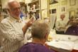 Happy man cutting senior customer's hair with razor