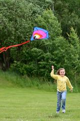 Child girl runs with kite
