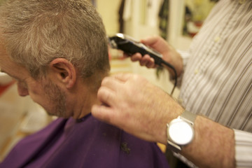 Midsection of senior barber giving haircut to customer in salon