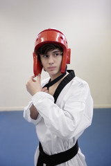 Teenage boy wearing martial arts headgear while looking away