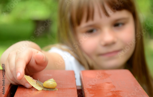 Child girl feeding snail