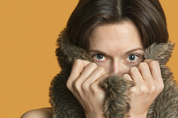 Portrait of a woman hiding with fur