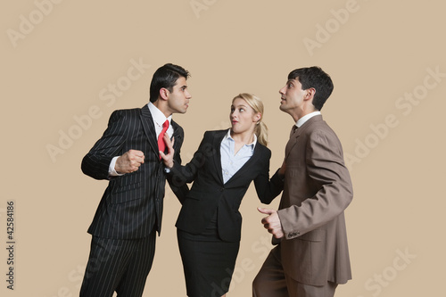 Furious businessmen in conflict with woman trying to resolve over colored background