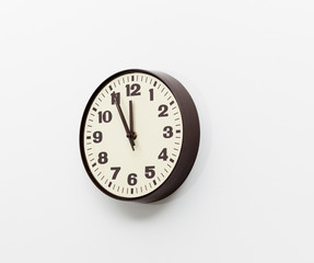 Brown clock on white office wall near noon