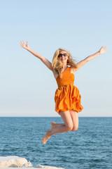 Frau springt am Strand