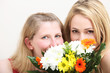 Two blonde women with flowers