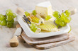 Cheese and grapes on wooden platter