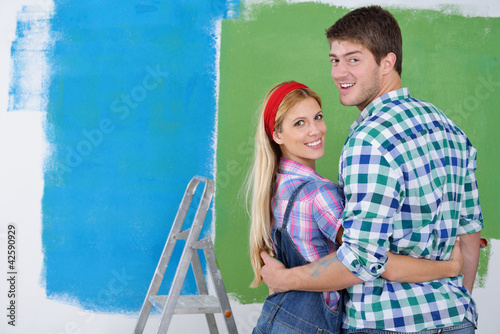 happy couple paint wall at new home