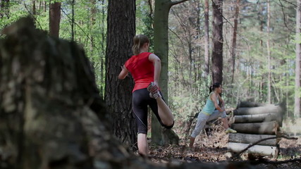 Two young women exercising and stretching in the forest