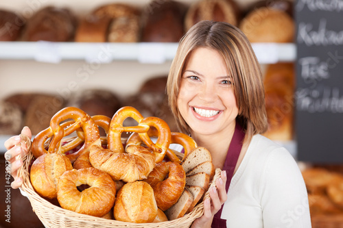 lächelnde verkäuferin hält brotkorb