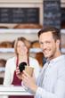 zufriedener kunde mit kaffee in der bäckerei