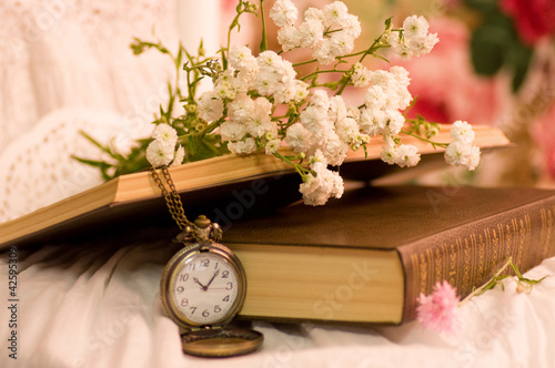 Antique pocket watch,opened old books and flowers