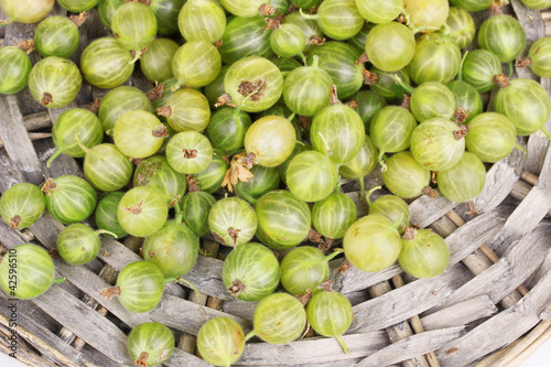 Green gooseberry on wicker mat close-up