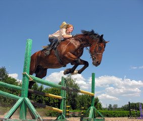 young cowgirl jumping with chestnut horse