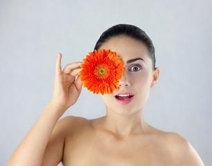 Zaskoczona i wesoła kobieta trzymająca kwiat obok twarzy