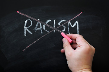 Cross out racism on a smudged blackboard background