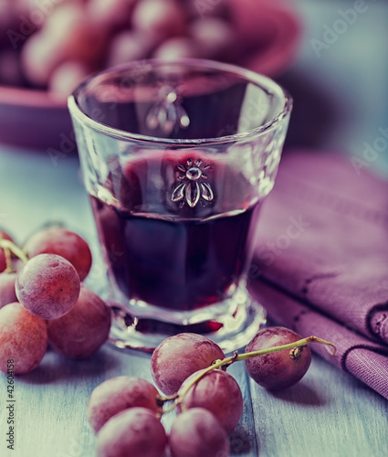 Glass of red wine and grapes on the table