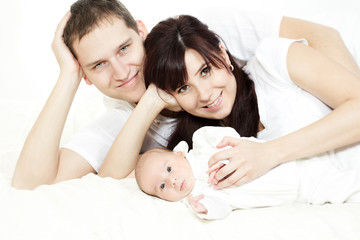 Happy family, parents embracing newborn baby