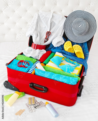 Red travel suitcase packed for vacation with personal belongings