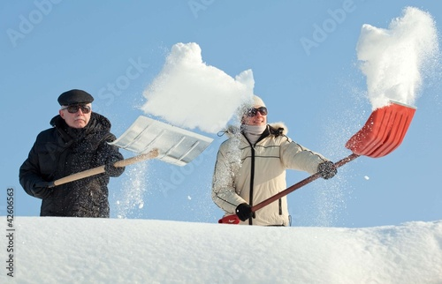 People shovelling snow on a roof