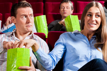 Couple in cinema theater with popcorn