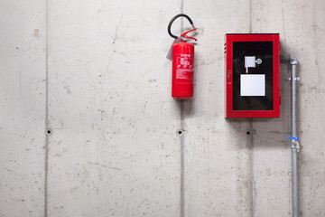 A fire extinguisher and a fire-hose on concrete wall