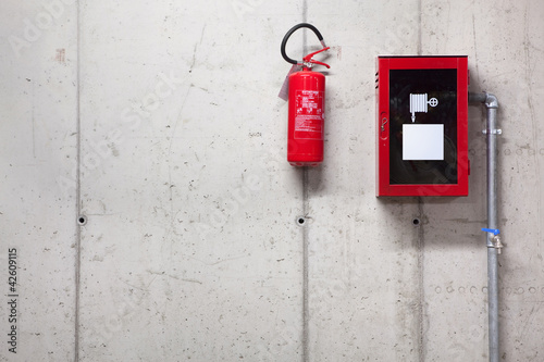 A fire extinguisher and a fire-hose on concrete wall - 42609115