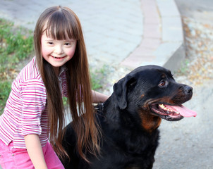 Smiling little girl with a big black dog