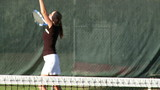 Girl serving tennis ball in slow motion