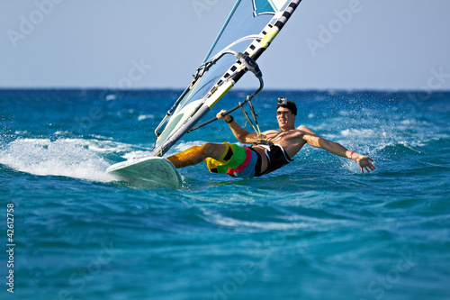fototapeta na ścianę Młody mężczyzna surfing wiatr w spryskane wodą